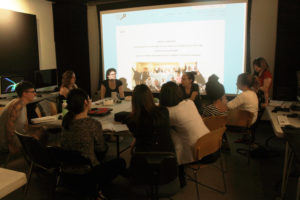 a group of participants sits around a table during a presentation