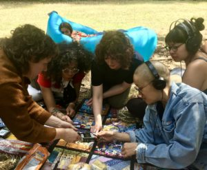 five people gather on a colourful quilt, around a field recorder. They are chaining headphones. A sixth person peeks out in the background from an inflated picnic lounge chair